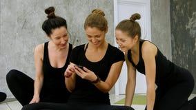 浏览互联网的三个少妇使用智能手机在锻炼以后在瑜伽类 免版税库存照片