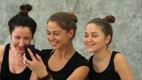 浏览互联网的三个少妇使用智能手机在锻炼以后在瑜伽类 股票录像