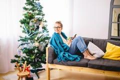 浏览在她的智能手机的妇女,当坐一个轻松的长沙发时 库存图片