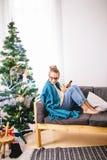 浏览在她的智能手机的妇女,当坐一个轻松的长沙发时 免版税库存图片