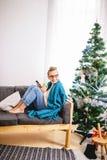 浏览在她的智能手机的妇女,当坐一个轻松的长沙发时 免版税图库摄影