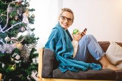 浏览在她的智能手机的妇女,当坐一个轻松的长沙发时 库存照片