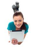 浏览在她的片剂个人计算机的俏丽的女孩 免版税库存照片
