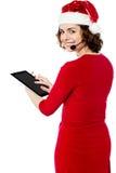 浏览在她的片剂个人计算机的女性圣诞老人 免版税库存照片