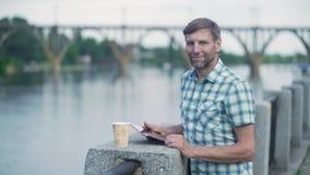 浏览在数字片剂的成熟人在夏天,在河码头 股票录像