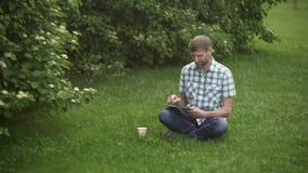 浏览在数字片剂的成熟人,坐草在公园 股票录像