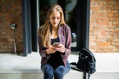 浏览在智能手机的社会网络的年轻美丽的微笑的适合的妇女,当基于台阶时 免版税库存照片