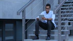 浏览在片剂个人计算机,当年轻黑人坐台阶时 免版税库存照片