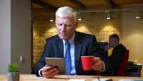 浏览在片剂和饮用的咖啡的老白种人商人特写镜头射击户内在的办公室 影视素材