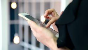 浏览她全新的智能手机的黑女衬衫的夫人互联网 股票视频