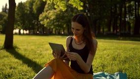 浏览她的片剂的少女在公园 股票录像
