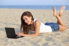 浏览她的netbook计算机的美丽的少年女孩说谎在海滩的沙子 免版税图库摄影