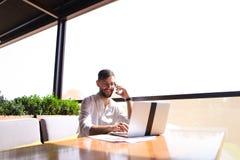 浏览新的信息的负责任的地产商由膝上型计算机和calli 免版税库存图片
