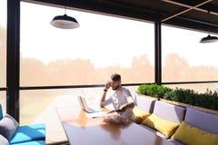 浏览新的信息的负责任的地产商由膝上型计算机和calli 免版税库存照片