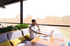 浏览新的信息的负责任的地产商由膝上型计算机和calli 库存照片