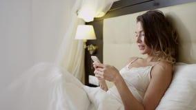 浏览智能手机的性感的妇女互联网在床上 股票视频