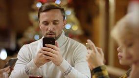 浏览智能手机的男人、妇女和小男孩互联网由Xmas充分的桌,关闭射击 影视素材