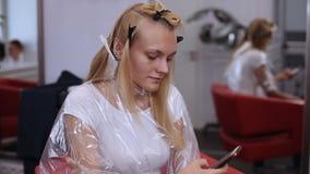 浏览有她的智能手机的一名白肤金发的妇女互联网在头发演播室 股票视频