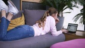 浏览的牛仔裤和的运动鞋的年轻女人说谎在长沙发和键入的文本在键盘笔记本或 美女使用 股票录像