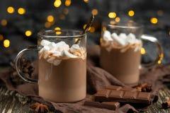浓冬天巧克力热饮用肉桂条和核桃,在一个透明杯子的巧克力块在一个木板,选择聚焦 免版税图库摄影