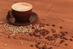 浓咖啡和溢出的coffed豆在一张egraved桌上 图库摄影