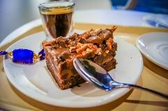 浓咖啡咖啡、巧克力软糖和巧克力蛋糕在有匙子的一块白色板材服务 库存图片