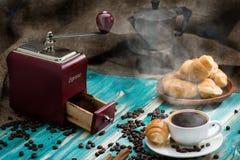 浓咖啡咖啡杯用与蒸汽的豆在一木桌stil 免版税库存图片