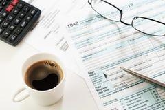 浓咖啡杯子、收入税单形式与计算器,玻璃和笔在桌上 库存照片