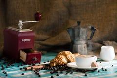 浓咖啡杯子热的咖啡和新月形面包在木背景 免版税图库摄影