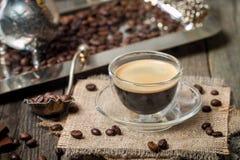 浓咖啡玻璃杯子用咖啡豆 库存照片