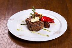 浓牛排用迷迭香和油煎的菜乳酪在白色板材 库存图片