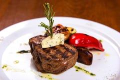 浓牛排用迷迭香和油煎的菜乳酪在白色板材 免版税库存图片