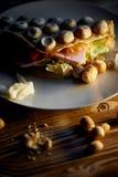 浓香港奶蛋烘饼用乳酪,火腿,莴苣,蕃茄 在黑暗的木背景 疏散胡说和干乌贼 图库摄影