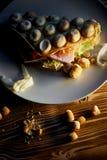 浓香港奶蛋烘饼用乳酪,火腿,莴苣,蕃茄 在黑暗的木背景 疏散胡说和干乌贼 免版税库存图片