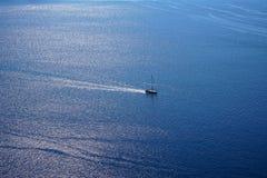 浩大的蓝色爱琴海海景拷贝空间背景看法与帆船的和海洋浇灌从Oia村庄的阳光反射 库存照片