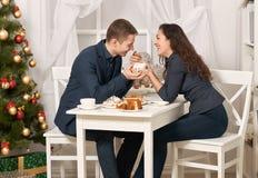 浪漫与曲奇饼和谈话的夫妇饮用的茶,与假日装饰,新年题材的圣诞树 免版税库存照片