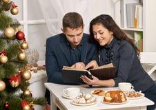 浪漫与曲奇饼和谈话的夫妇饮用的茶,与假日装饰,新年题材的圣诞树 库存图片