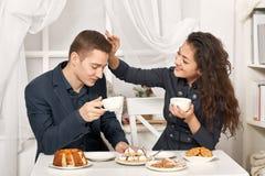 浪漫与曲奇饼和谈话的夫妇饮用的茶 免版税库存照片