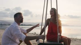 浪漫享受海洋日落的新婚佳偶愉快的年轻夫妇 股票录像