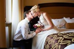 浪漫亲吻新娘和新郎在卧室 免版税库存图片