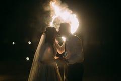浪漫亲吻与在火焰状心脏前面的夫妇结婚 夜射击 免版税库存图片