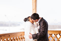 浪漫亲吻愉快的新娘和新郎在冬天婚礼之日 免版税库存照片