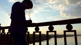浪漫人在河桥梁站立并且写他的想法下来在日落 股票视频