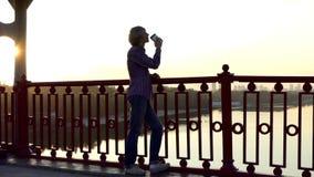 浪漫人在Slo Mo喝咖啡并且享受在一座桥梁的日落 股票录像