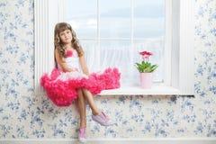 浪漫作的女孩坐窗台 免版税库存图片
