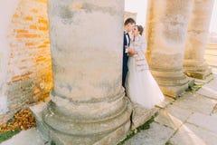 浪漫全lengthportrait拥抱的新婚佳偶和身分在专栏附近 免版税图库摄影