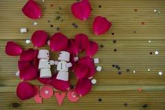 浪漫冬天季节摄影图象用作为与微笑的雪人被塑造的蛋白软糖在冰了在红色玫瑰花瓣 免版税图库摄影