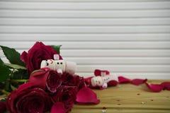浪漫冬天季节摄影图象用作为与微笑的雪人被塑造的蛋白软糖在冰了在红色玫瑰花瓣 免版税库存照片