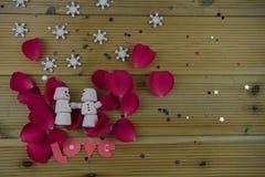 浪漫冬天季节摄影图象用作为与微笑的雪人被塑造的蛋白软糖在放置冰了在红色玫瑰花瓣 图库摄影