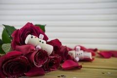 浪漫冬天季节摄影图象用作为有微笑的睡觉的雪人被塑造的蛋白软糖在冰了在红色玫瑰花瓣 免版税库存图片
